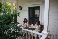 Two women enjoying wine in robes